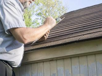 A man inspecting a house roof